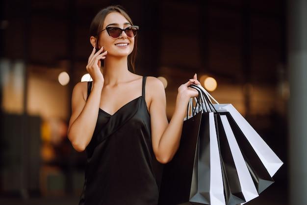Femme à La Mode Vêtue D'une Robe Noire Avec Des Sacs à Provisions. Photo Premium