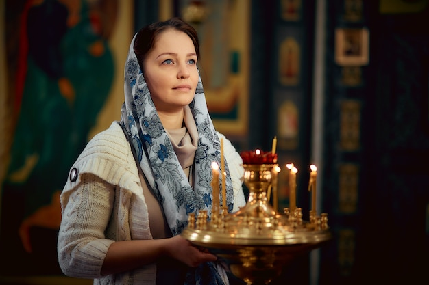 Femme de mode de vie allume des bougies dans l'église, priant devant l'icône Photo Premium