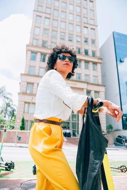 Femme moderne dans une ville avec un scooter électrique Photo gratuit