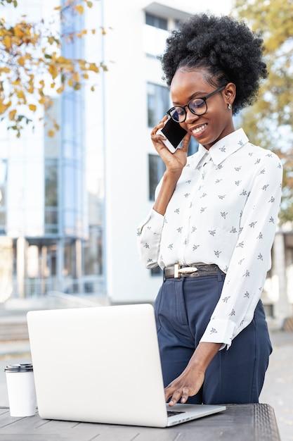 Femme Moderne Travaillant Sur Un Ordinateur Portable Et Parlant Au Téléphone Photo gratuit