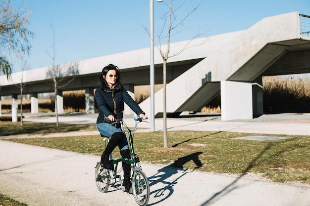 Femme moderne à vélo dans la ville Photo gratuit