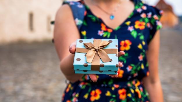 Femme Montrant Un Cadeau Dans La Rue Photo gratuit