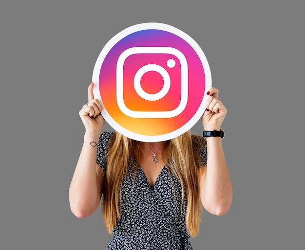 Femme montrant une icône instagram Photo gratuit