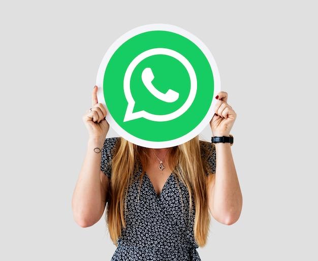 Femme montrant une icône whatsapp messenger Photo gratuit
