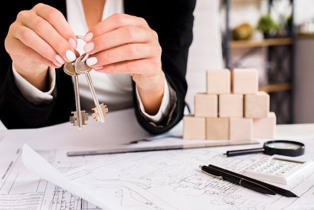 Femme montrant un jeu de clés Photo gratuit