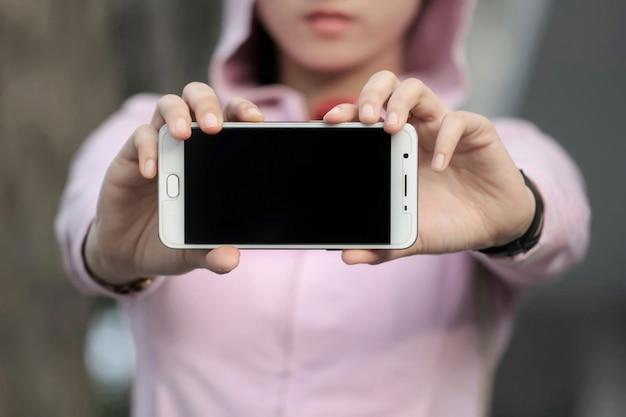 Une femme montre un écran tactile mobile Photo Premium