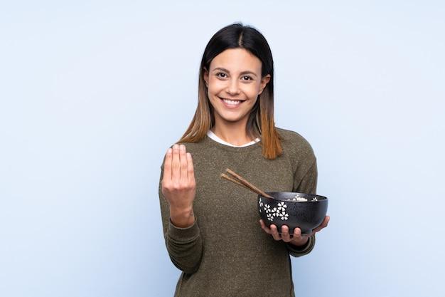 Femme Sur Mur Bleu Isolé Invitant à Venir Avec La Main. Heureux Que Tu Sois Venu En Tenant Un Bol De Nouilles Avec Des Baguettes Photo Premium