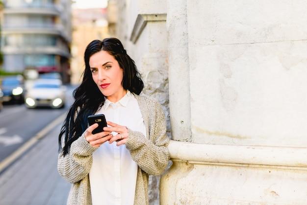Femme mûre confuse et perdue en consultant son téléphone portable. Photo Premium