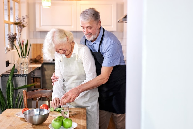Femme Mûre, Préparer Le Repas, Son Mari L'aide De L'arrière, Découpant Des Légumes Photo Premium