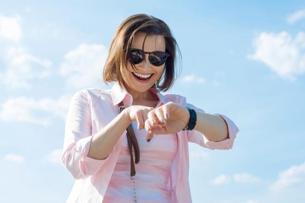Femme mûre regarde l'horloge, l'émotion de la joie Photo Premium