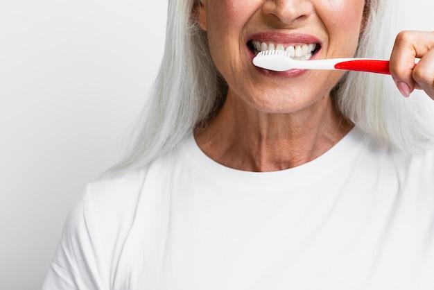 Femme mûre se nettoyant les dents Photo gratuit
