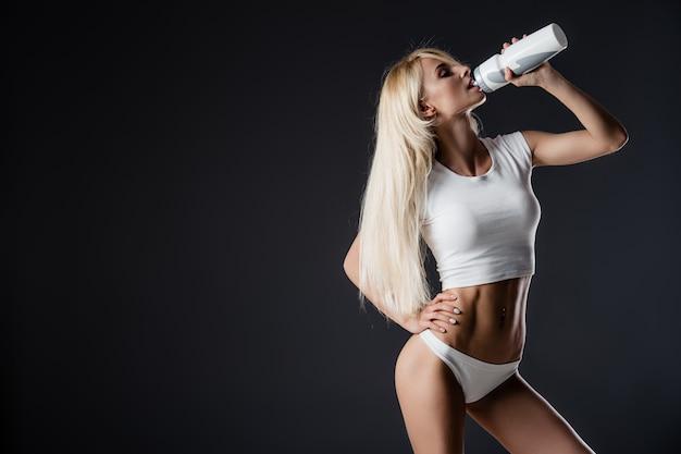 Femme Musclée Sportive Eau Potable, Isolée Contre Gris Photo Premium