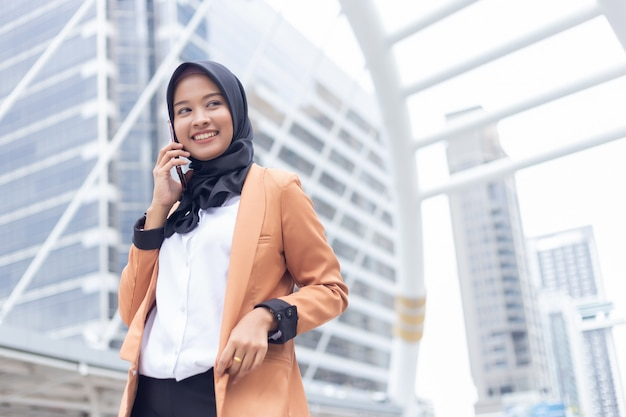 Femme musulmane d'affaires utilisant le téléphone en ville. Photo Premium