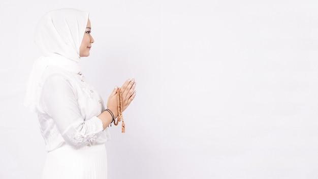 Femme Musulmane Asiatique Portant Des Perles De Prière Accueillant Les Invités Ou Ied Fitr Voeux Dans L'espace Blanc Photo Premium