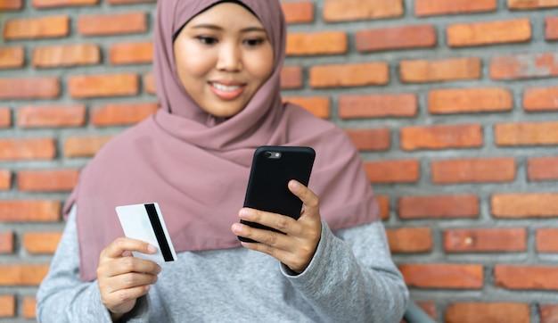 Femme musulmane détenant un mobile et une carte de crédit pour faire du shopping en temps de détente Photo Premium