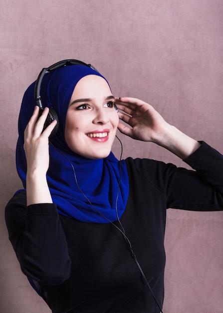 Femme musulmane écoutant de la musique sur des écouteurs Photo gratuit