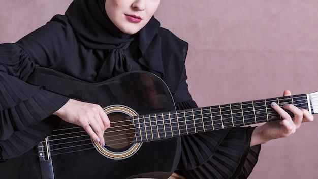 Femme musulmane jouant de la guitare Photo gratuit