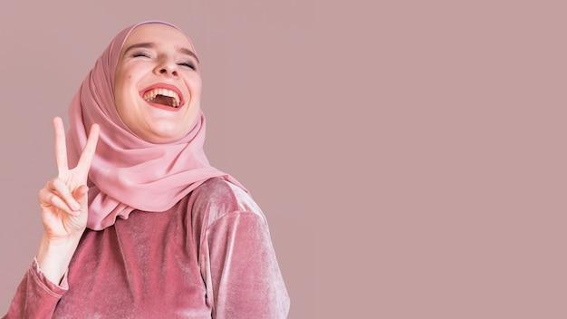 Femme musulmane joyeuse gesticulant signe de la paix sur fond de studio Photo gratuit