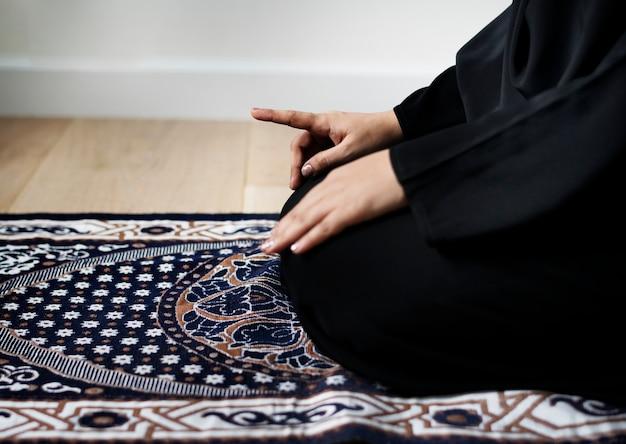 Femme musulmane priant dans la posture de tashahhud Photo Premium