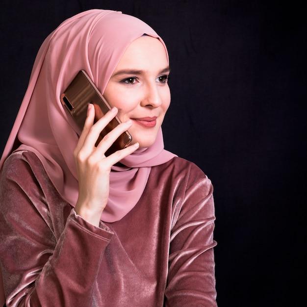 Femme musulmane souriante parlant sur téléphone mobile sur fond noir Photo gratuit