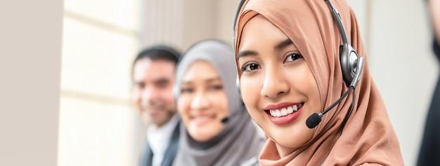 Femme musulmane travaillant en tant qu'opérateur de service clientèle avec l'équipe du centre d'appels Photo Premium