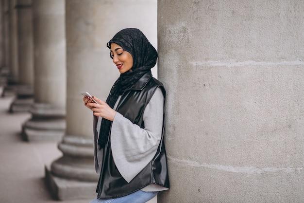 Femme musulmane utilisant un téléphone à l'extérieur dans la rue Photo gratuit
