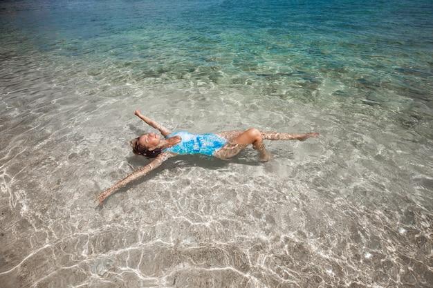 Femme nageant sur le dos en mer Photo Premium