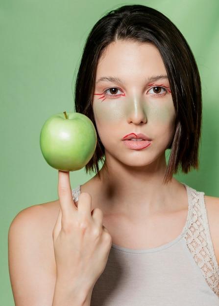 Femme naturelle équilibrant la pomme sur le doigt Photo gratuit