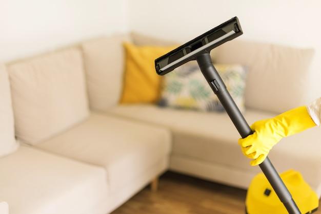 Femme nettoyant un canapé avec un aspirateur jaune. concept propre Photo Premium
