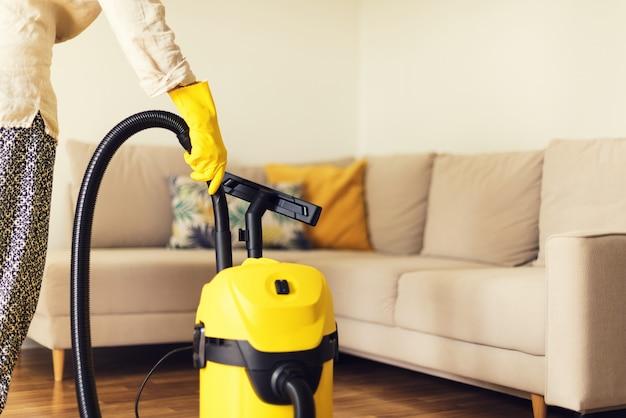 Femme nettoyant un canapé avec un aspirateur jaune. espace de copie. concept de service de nettoyage Photo Premium