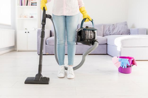Femme nettoyant sa maison avec un aspirateur Photo gratuit