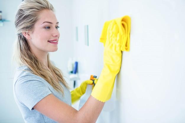Femme nettoyant la salle de bain dans sa maison Photo Premium