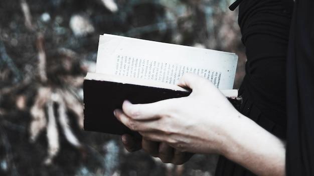 Femme en noir avec livre ouvert Photo gratuit