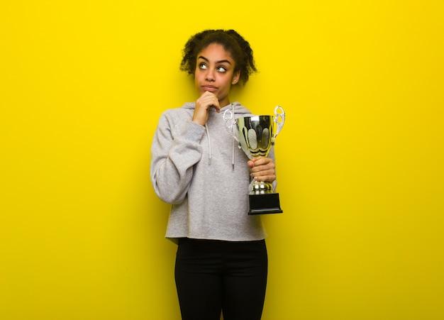 Femme noire jeune fitness pensant à une idée. tenant un trophée. Photo Premium