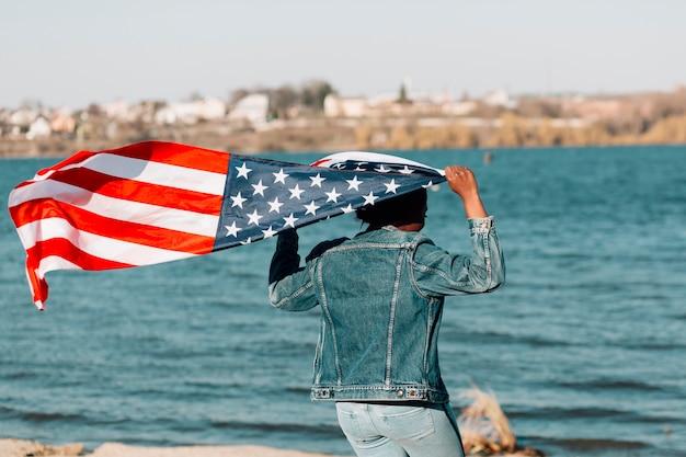 Femme noire rebroussée tenant le drapeau américain Photo gratuit