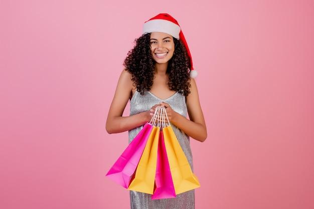 Femme noire avec des sacs à provisions jaunes et roses portant chapeau de noël isolé Photo Premium
