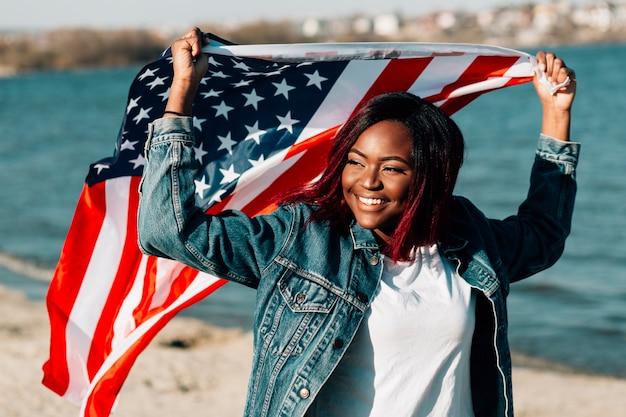 Femme noire tenant un drapeau américain au-dessus de la tête Photo gratuit