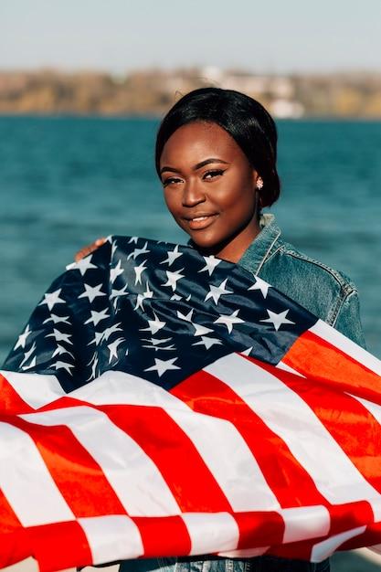 Femme noire, tenant drapeau américain Photo gratuit