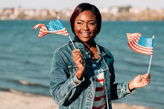 Femme noire, tenant drapeaux américains, dans, mains Photo gratuit