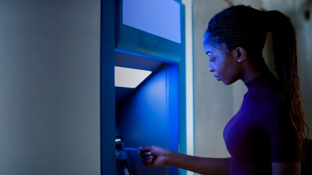 Femme noire utilisant le guichet automatique Photo Premium