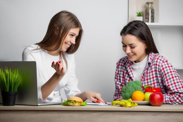 Femme En Nutritionniste En Blouse Blanche écrit Un Programme D'alimentation Saine Pour Perdre Du Poids Photo Premium