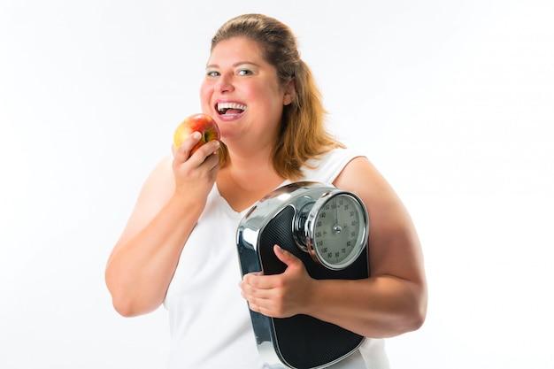 Femme obèse avec écaille sous le bras et pomme Photo Premium