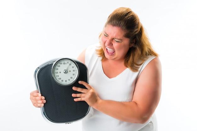 Femme Obèse Regardant En Colère à L'échelle Photo Premium