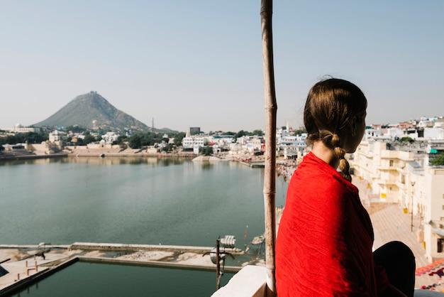 Femme occidentale bénéficiant d'une vue sur le lac pushkar au rajasthan Photo gratuit