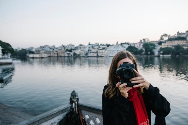 Femme occidentale capturant une vue sur la ville d'udaipur, en inde Photo gratuit