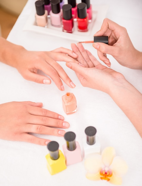 Femme ongles avec du vernis à ongles sur une serviette blanche et douce. Photo Premium