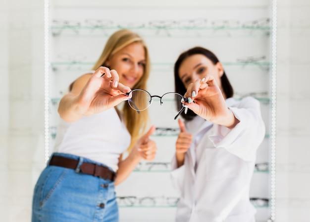 Femme, et, opticien, tenir lunettes, monture Photo gratuit