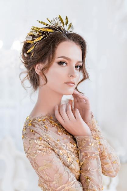 Femme en or soirée gawn et couronne pose dans la chambre blanche de luxe Photo gratuit