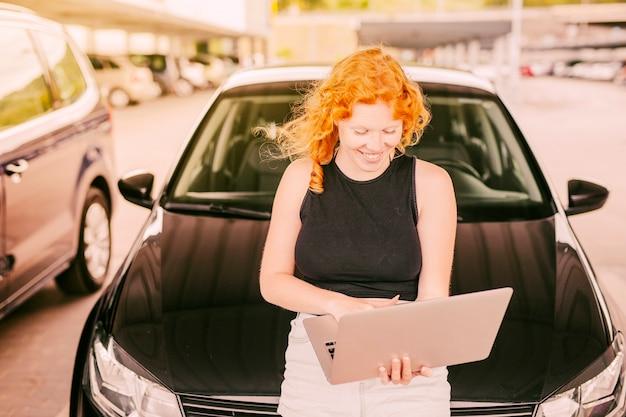 Femme avec ordinateur portable assis sur le capot de la voiture Photo gratuit