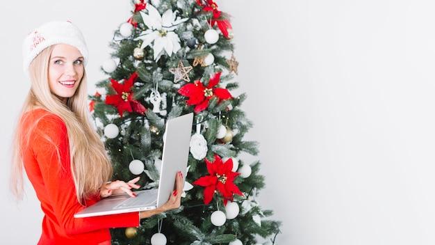 Femme, à, ordinateur portable, près, arbre noël Photo gratuit